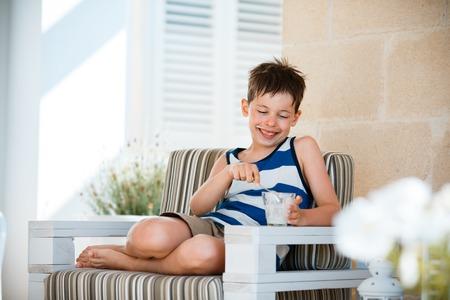 junky: Portrait of smiling little boy eating delicious yogurt on outdoor terrace