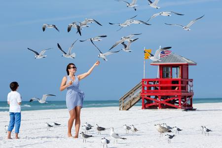 gaviota: Joven madre y su pequeño hijo alimentación gaviotas en la playa tropical, vacaciones de verano vacaciones en Florida