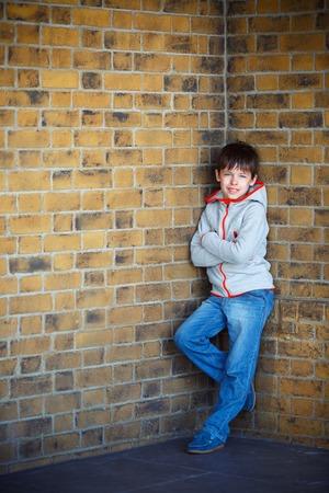 7 8 years: Portrait of cute little boy near brick wall outdoors