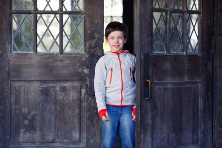 7 8 years: Portrait of cute little boy near wooden door outdoors
