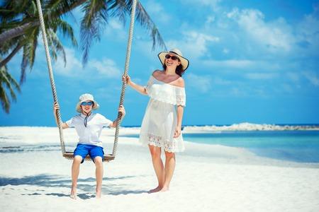 Giovane bella donna che fa oscillare suo figlio su una spiaggia tropicale, isola di Koh Phangan. Thailandia, Asia