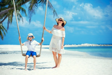 Mujer hermosa joven que hace pivotar a su hijo en una playa tropical, isla de Koh Phangan. Tailandia, Asia