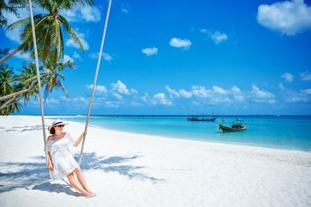 phangan: Beautiful woman swinging on a Tropical beach on Koh Phangan island. Thailand, Asia Stock Photo