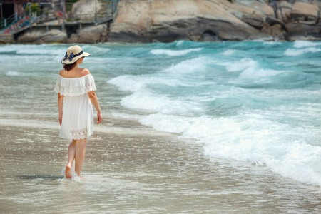 clothe: Woman with white clothe walking on the beach  during summer vacation