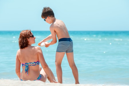 mom son: Son applying sunblock cream on his mother shoulder during summer vacation