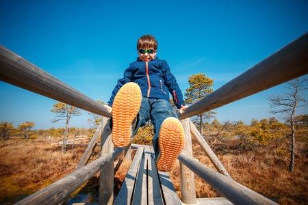 Cute little boy walking on trail in swamp, Kemeri national park, Latvia