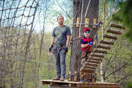 clambering: Cute little boy and his father enjoying time in climbing adventure park
