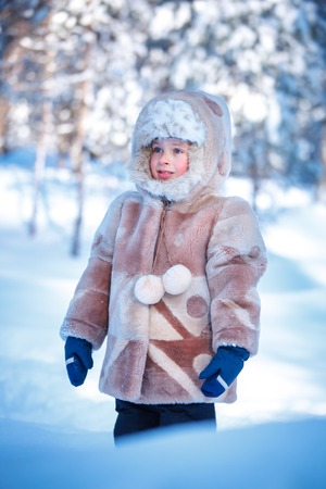 Portrait of little boy playing outdoors in forest on beautiful winter snowy day