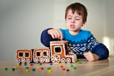 christmas train: Happy boy with christmas train made of gingerbread indoors