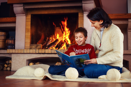 fireplace home: Mother and her little son by a fireplace at home Stock Photo