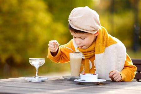 tomando leche: El niño pequeño lindo beber chocolate caliente en café al aire libre en el hermoso día de otoño
