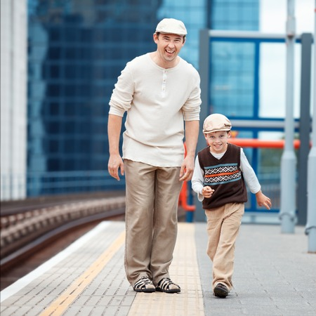 Young father and son on railway station platform Stock Photo