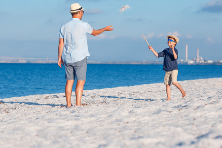 Happy father and his son having fun at the beach