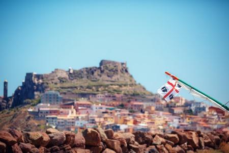 moors: Traditional Four Moors flag of Sardinias Region against Medieval town Castelsardo Stock Photo