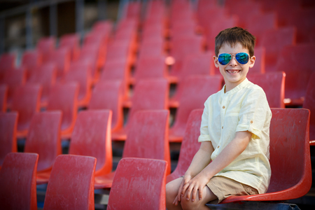 Cute little boy sits on a tribune Stock Photo