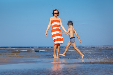 Mother and son having fun on beach during summer holiday vacation