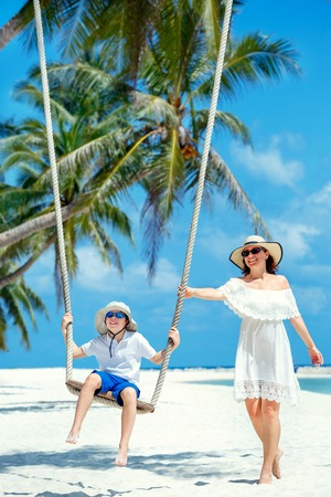 Young beautiful woman swinging son on a tropical beach, Koh Phangan island. Thailand.