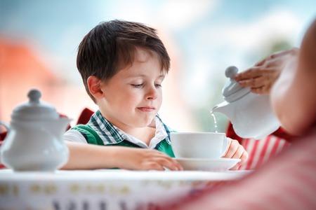 Cute little boy drinking tea in cafe
