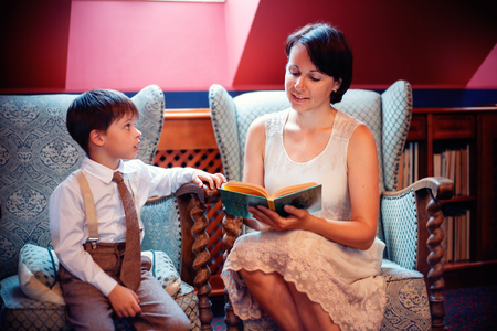 Yoing mother and her little son reading a book