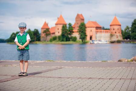 Little boy in front of Trakai Castle in Lithuania