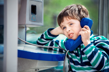 Cute little boy is calling home using the public payphone Фото со стока