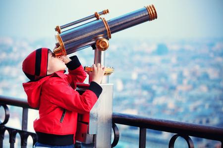 Child looking through coin operated high powered binoculars on a scenic cityscape of Paris