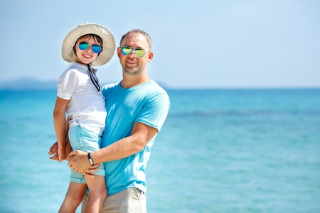 Happy father and his cute little son on a tropical beach