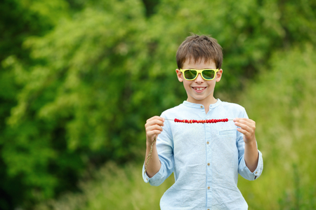 Cute little boy enjoying summer wild strawberries on straw