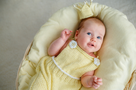 Newborn baby girl lying in a basket with crown and yellow bodysuit