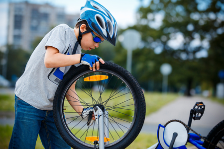 Cute little boy repairing bicycle outdoors Stock Photo