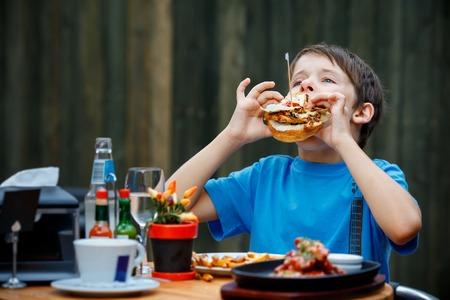 Cute healthy teenager boy eats hamburger and potato Stock Photo