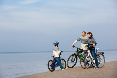 Young family of three riding bicycles on beach 版權商用圖片