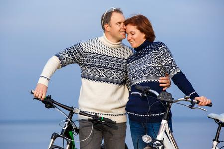 Cheerful couple biking on a sand beach