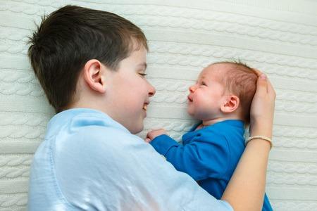 Big brother hugging his newborn baby girl. Toddler kid meeting new sibling
