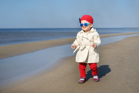Happy little girl running on Baltic Sea beach in Latvia. Kids play in ocean sand dunes on cold autumn or spring day