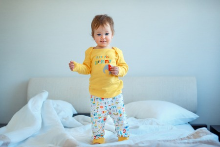 Funny little baby girl standing in parents bed. Infant girl in yellow pajamas Stock Photo