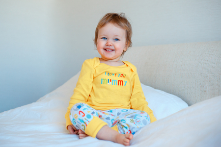 Funny little baby girl sitting in parents bed. Infant girl in yellow pajamas