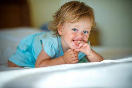 Lovely blonde toddler girl lying at home or kindergarten on a bed Banque d'images