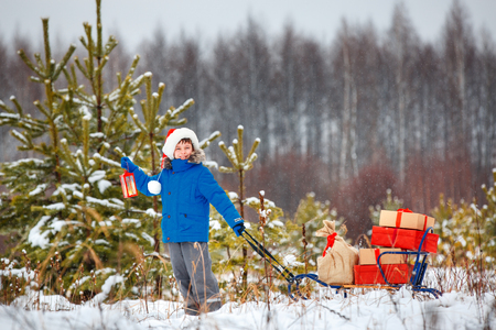 Cute little boy in Santa hat carries a wooden sled with gifts in snowy forest