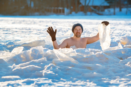 Winter swimming. Brave man in an ice-hole
