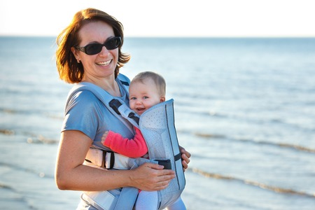 Baby and mother on sea at summer day. Child in a carrier backpack Stock Photo