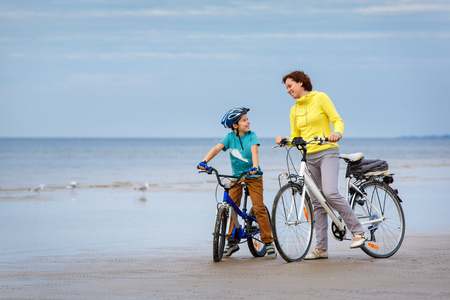 Young mother with her little son riding bicycles on beach Stok Fotoğraf