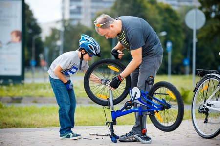 Cute little boy with his father repairing bicycle outdoors