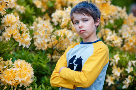 Outdoor spring portrait of unhappy 10 year old boy posing in the garden next to blossoming yellow Rhododendron