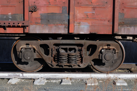 The car of an old rusty freight train stands on the rails; only part of the car in the foreground can see overgrown dry vegetation