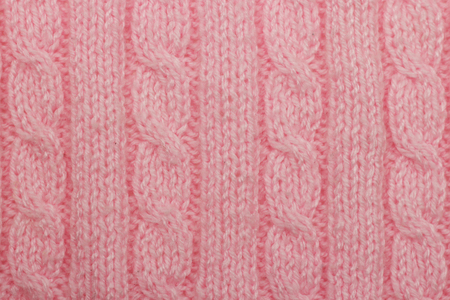 Pink knitted background vertical columns and braids hobby leisure activity creativity