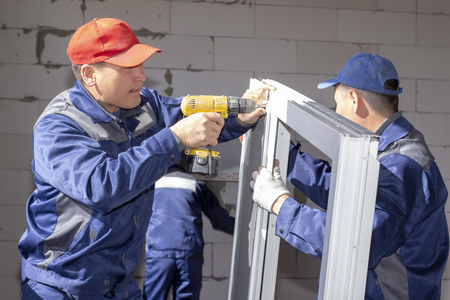 workers install glazing in a house under construction, make measurements, drill, saw grinder Standard-Bild - 121756001