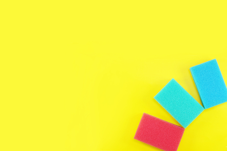 yellow background on the theme of cleaning with colorful sponges with copyspace