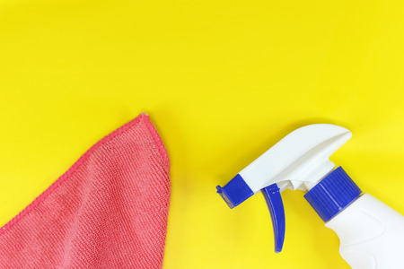 yellow background on the theme of cleaning with a spray and a rag with copyspace