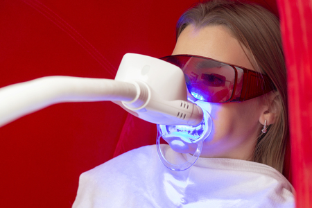 teeth whitening girl sits with aparts on teeth for teeth whitening in protective glasses